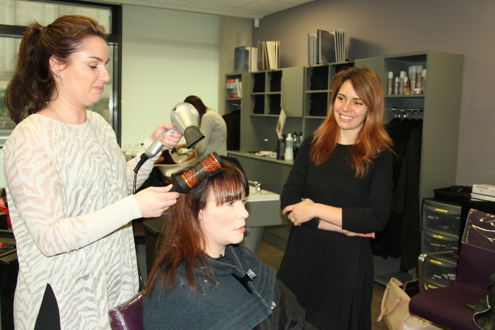 Chelsea Larkin of Precious Hair and Beauty Lounge styles her business partner and Natalie Dewhirst's hair, watched by Amy Sontae of Wella.